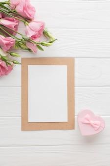 Vista superior de rosas rosadas con pequeña caja de regalo