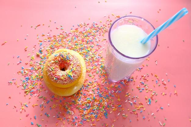 Vista superior de rosquillas y leche en rosa.