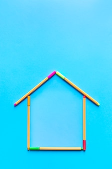 Vista superior de rotuladores fluorescentes formando un dibujo de una casa sobre fondo azul pastel.