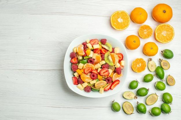 Vista superior sabrosa ensalada de frutas con feijoas frescas sobre fondo blanco.