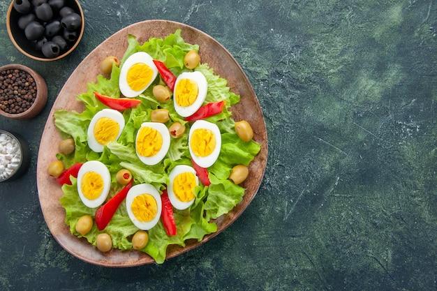 Vista superior sabrosa ensalada de huevo con ensalada de aceitunas verdes y condimentos sobre fondo azul oscuro
