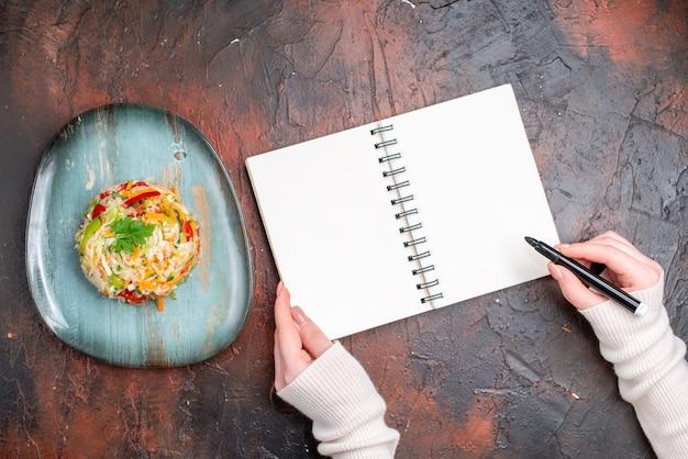 Vista superior sabrosa ensalada de verduras dentro de la placa con dibujo de mujer sobre la mesa oscura