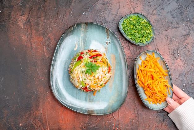 Vista superior sabrosa ensalada de verduras dentro de la placa con verduras y zanahoria en la mesa oscura
