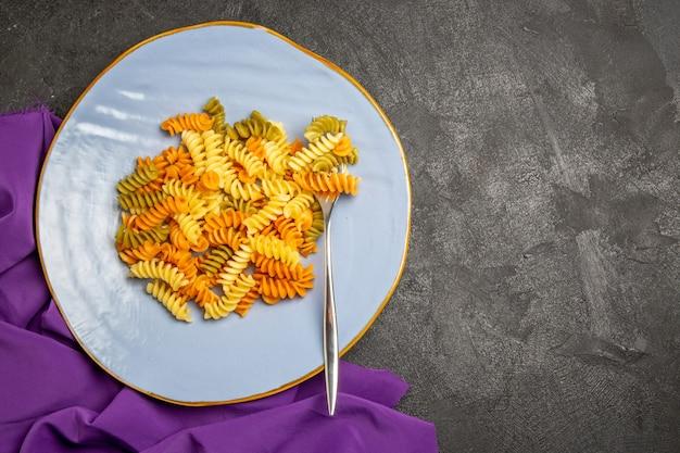 Vista superior sabrosa pasta italiana pasta espiral cocida inusual en gris