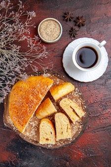 Vista superior sabrosa pastelería dulce cortada en trozos con té sobre una superficie oscura