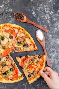 Vista superior de la sabrosa pizza de queso en rodajas y servida en una superficie gris