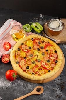 Vista superior de la sabrosa pizza con queso con tomates rojos, aceitunas negras y salchichas en el escritorio oscuro con aceite y tomates frescos, masa italiana de comida rápida