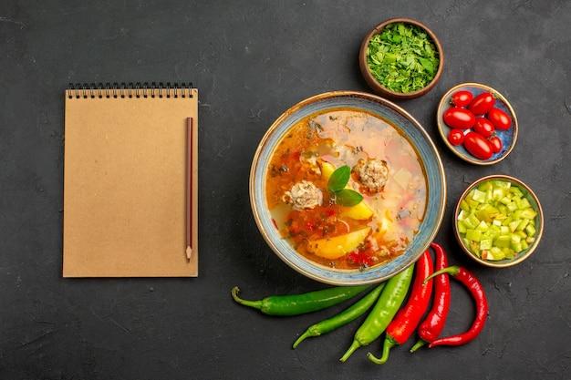 Vista superior sabrosa sopa de albóndigas con verduras y pimienta en el color del plato de salsa de mesa oscura