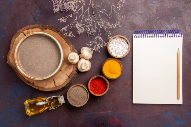 Vista superior sabrosa sopa de champiñones con diferentes condimentos en la comida de condimentos de sopa de escritorio de color púrpura oscuro