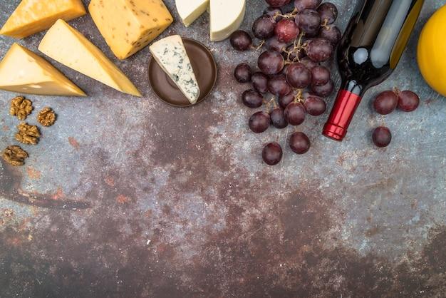 Vista superior sabrosa variedad de queso con uvas y botella de vino