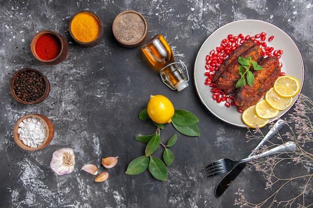 Vista superior sabrosas chuletas de carne con condimentos en la comida de la foto del plato de fondo gris