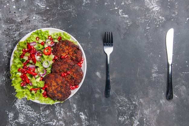 Vista superior sabrosas chuletas de carne con ensalada fresca en piso gris foto comida plato de carne