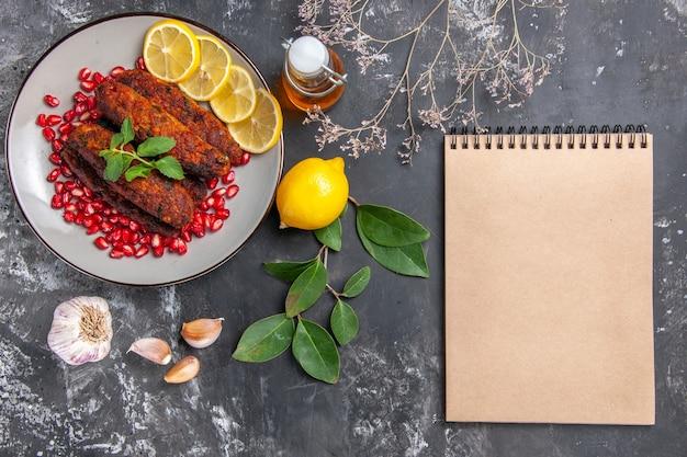 Vista superior sabrosas chuletas de carne con rodajas de limón en el fondo gris plato foto comida