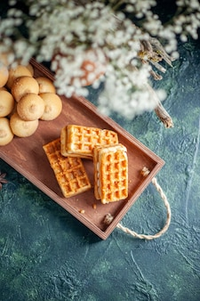 Vista superior sabrosas galletas dulces con pequeños pasteles dulces sobre fondo oscuro pastel dulce de color pastel de azúcar tuerca de galleta