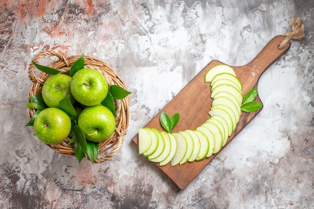Vista superior sabrosas manzanas verdes con frutas en rodajas sobre el fondo claro