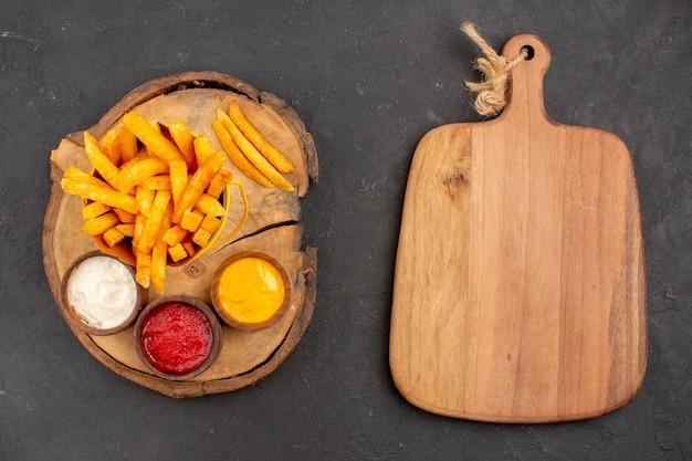 Vista superior de sabrosas papas fritas con salsas en gris