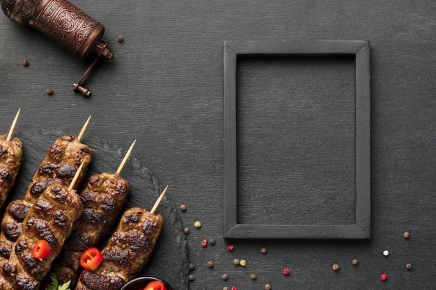 Vista superior del sabroso kebab con condimentos y marco
