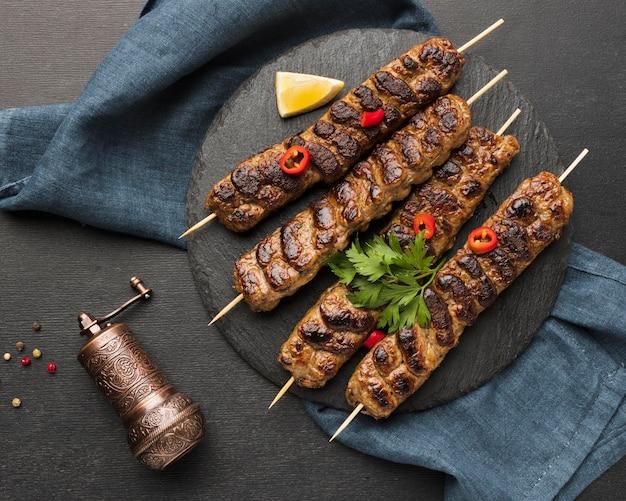 Vista superior del sabroso kebab en pizarra con molinillo de condimentos