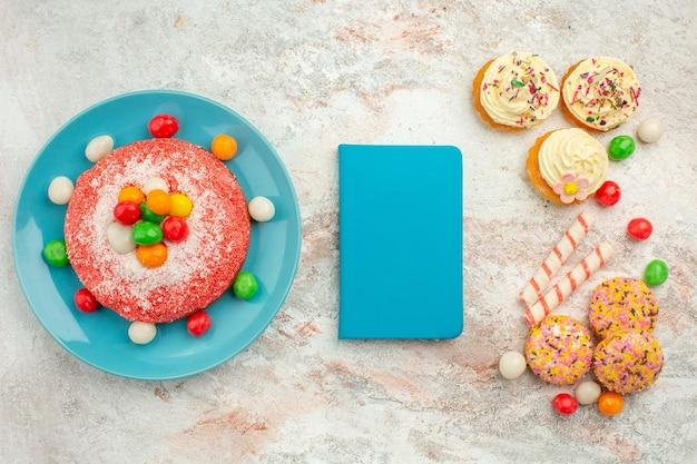 Vista superior sabroso pastel rosa con deliciosos pasteles de galleta en superficie blanca pastel de color de postre de caramelo de arco iris de golosinas