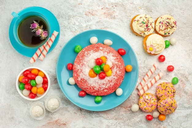 Vista superior sabroso pastel rosa con deliciosos pasteles de galleta y té en la superficie blanca pastel de color de postre de caramelo de arco iris de golosinas