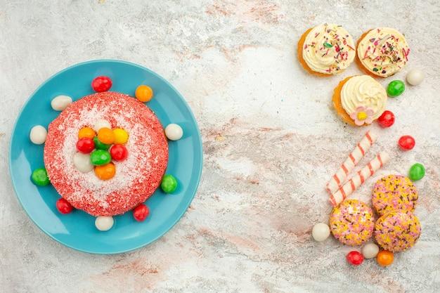 Vista superior sabroso pastel rosa con galletas en superficie blanca pastel de color de postre de caramelo de arco iris de golosinas