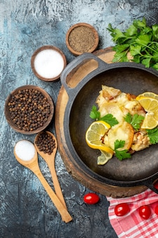 Vista superior sabroso pescado frito con limón y perejil en sartén sobre tablero de madera tomates cherry perejil sobre fondo gris