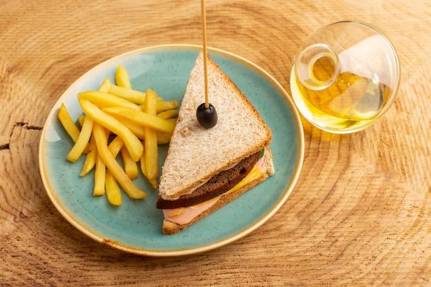 Vista superior sabroso sándwich con jamón de oliva tomates verduras dentro de un plato con papas fritas y aceite en el fondo de madera sándwich comida bocadillo desayuno