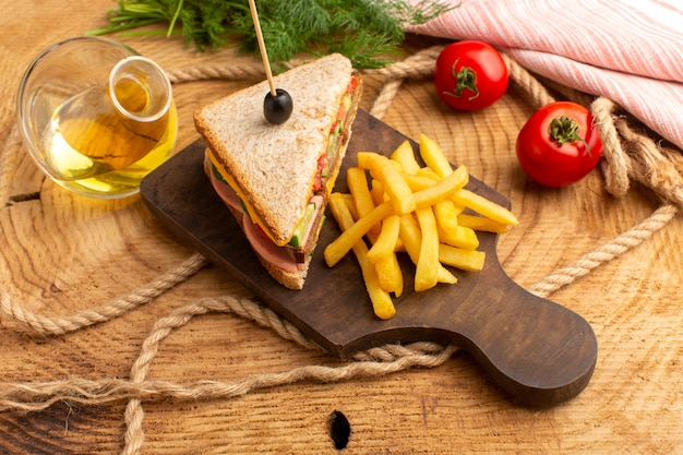 Vista superior sabroso sándwich con jamón de oliva tomates verduras junto con papas fritas cuerdas aceite tomates rojos en el fondo de madera sándwich comida merienda desayuno