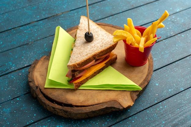 Vista superior sabroso sándwich con jamón de queso dentro con papas fritas en el escritorio de madera azul comida de sándwich