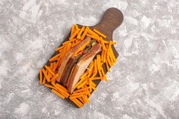 Vista superior sabroso sándwich de tostadas con jamón de queso junto con papas fritas en la comida de sándwich de fondo blanco