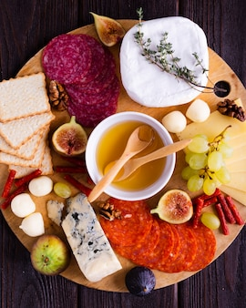 Vista superior sabrosos aperitivos en una tabla de madera