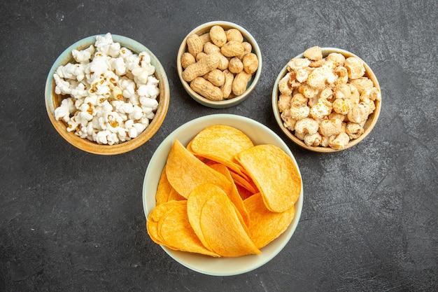 Vista superior de sabrosos chips de queso con diferentes bocadillos en el fondo oscuro