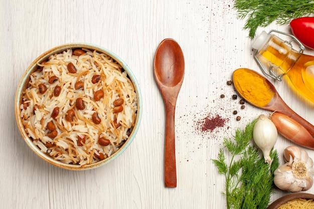 Vista superior de sabrosos fideos cocidos con frijoles en la mesa blanca clara