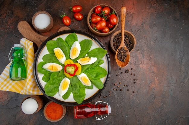 Vista superior sabrosos huevos duros con condimentos y tomates en la mesa oscura