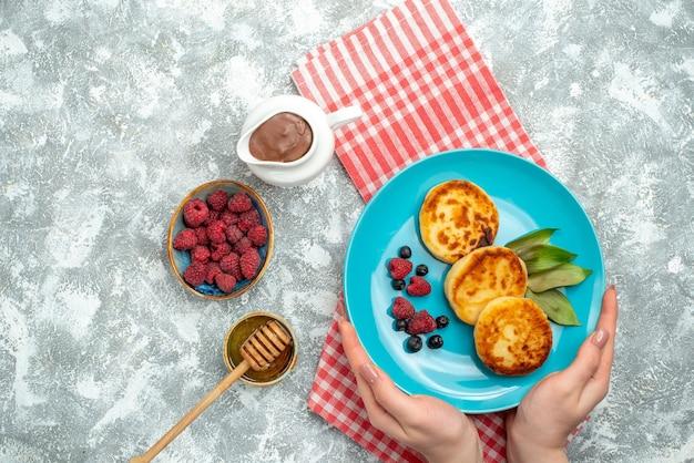 Vista superior de sabrosos muffins con bayas en la superficie clara