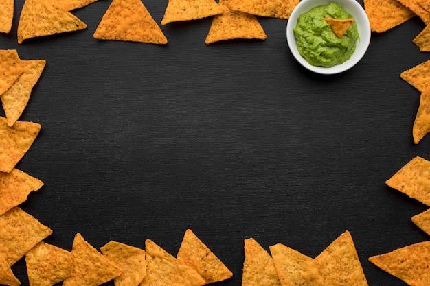 Vista superior sabrosos nachos con guacamole sobre la mesa