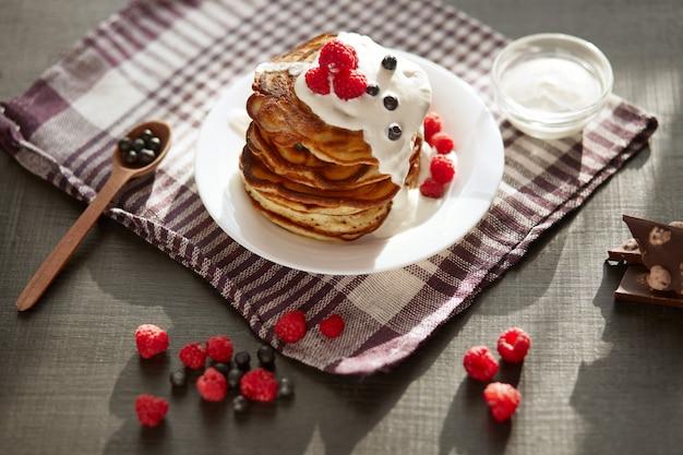 Vista superior de sabrosos panqueques con arándanos y frambuesas en la mesa de color marrón oscuro, taza de té o café, cuchara de madera con bayas frescas