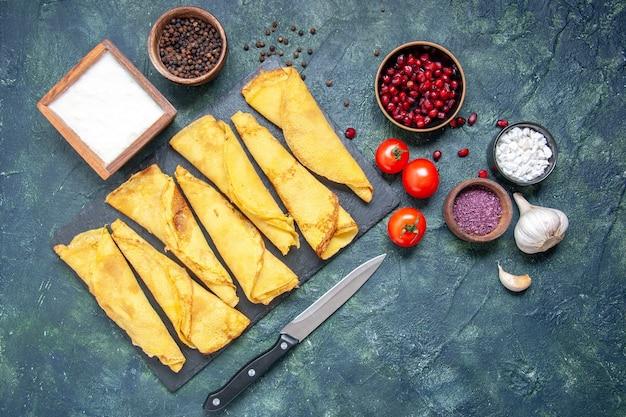 Vista superior sabrosos panqueques enrollados forrados con tomates sobre fondo oscuro hotcake color comida masa para tartas pastelería pastel dulce
