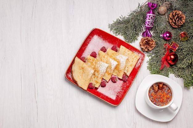 Vista superior de sabrosos panqueques con taza de té y frutas en blanco