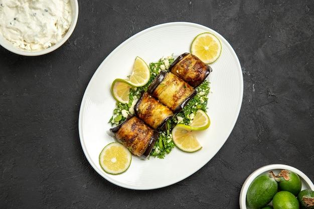 Vista superior de sabrosos rollos de berenjena plato cocido con rodajas de limón y feijoa en la superficie oscura cena aceite plato cocina comida