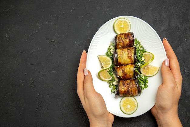 Vista superior de sabrosos rollos de berenjena plato cocido con rodajas de limón en la superficie oscura plato de comida de cocina de aceite de cena