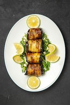 Vista superior de sabrosos rollos de berenjena con rodajas de limón en la superficie oscura plato de cena de comida de cocina de fruta