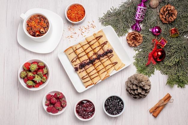 Vista superior de sabrosos rollos de panqueques con taza de té y frutas en blanco