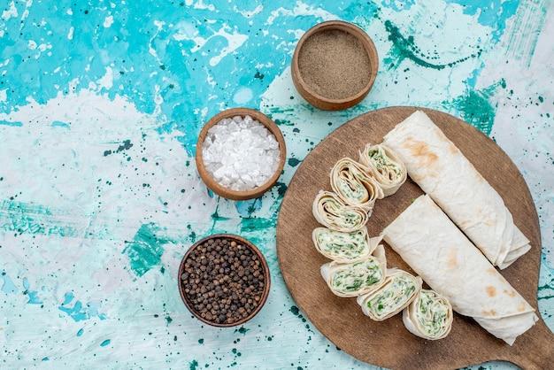 Vista superior de sabrosos rollos de verduras enteras y en rodajas con verduras y condimentos sobre el fondo azul brillante rollo de comida de color vegetal
