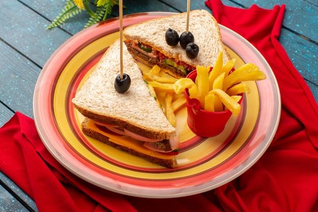 Vista superior sabrosos sándwiches dentro de placa colorida dentro de jamón de queso con papas fritas en el escritorio de madera azul comida de sándwich