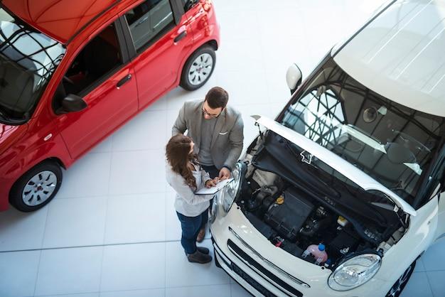 Vista superior de la sala de exposición de vehículos y personas que discuten sobre las especificaciones y el precio del automóvil en el concesionario local.
