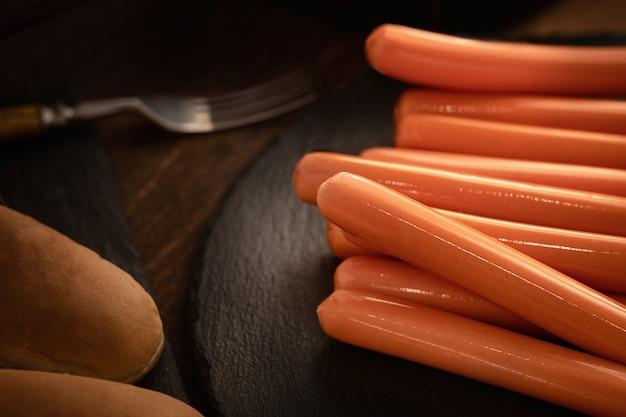 Vista superior de salchichas frescas para perros calientes en la oscuridad con bollos.