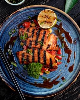 Vista superior de salmón a la plancha con verduras limón y salsa de soja en un plato sobre la mesa de madera