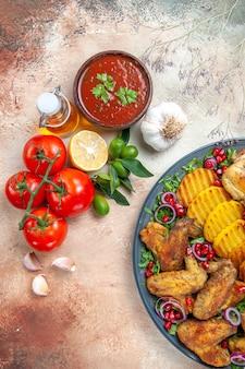 Vista superior de salsa salsa limón ajo plato de pollo patatas aceite tomates con pedicelos