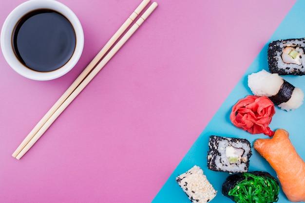 Vista superior de salsa de soja y rollos de sushi en la mesa